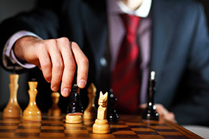 Leadership strategy illustrated by businessman playing chess game.